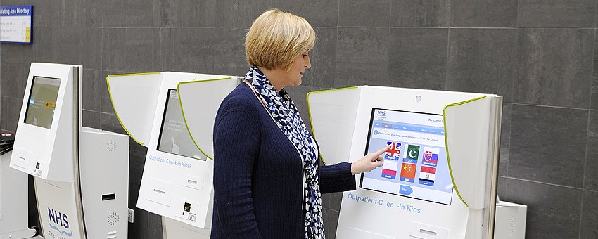 Female using self check-in at the QEUH